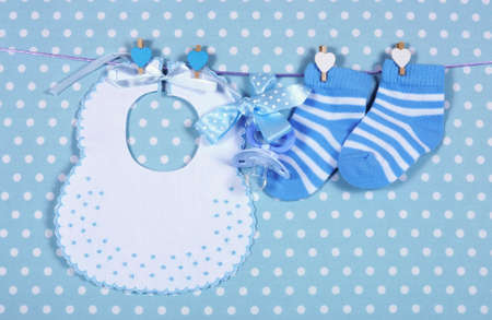 Baby boy nursery blue socks and bib, with dummy pacifier hanging from pegs on a line against a blue polka dot background for baby shower or newborn greeting card