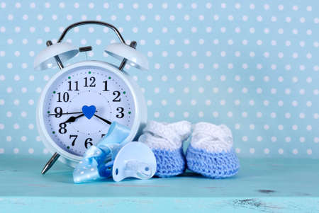 Baby boy nursery blue and white booties and clock, on aqua vintage shabby chic wood table and polka dot background for baby shower or newbornl greeting card