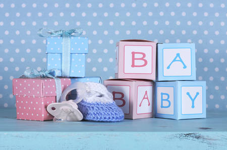 its: Baby nursery bootie, dummy pacifier and baby letters pink and blue gift boxes against a vintage aqua blue table and polka dot background for baby shower or newborn girl greeting card  Stock Photo