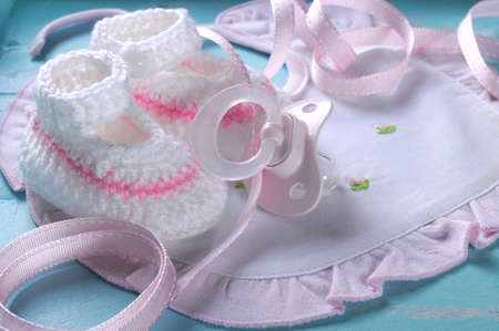 bonnet up: Close up of baby girl nursery dummy pacifier and pink and white wool booties and bonnet on aqua vintage shabby chic background for baby shower or newborn girl greeting card