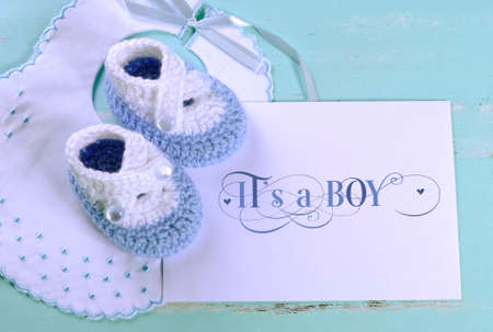 Baby boy nursery blue and white wool booties, bib and card with Its A Boy sample text, on aqua vintage shabby chic background for baby shower or newborn girl greeting card  Stock Photo