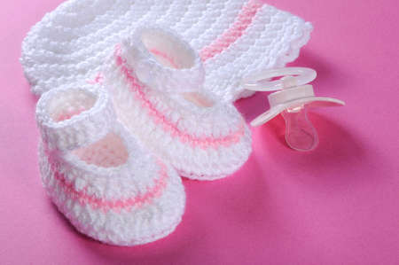 bonnet up: Close up of baby girl nursery pink and white stripe wool booties, bonnet and pacifier dummy on pink background for baby shower or newborn girl greeting card  Stock Photo