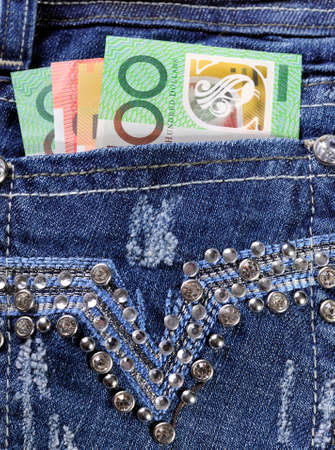 Australian hundred, fifty and twenty dollar notes in back pocket of feminine ladies rhinestone decorated jeans, for money in the pocket concept image, close up  photo