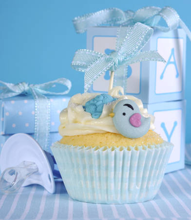Blue theme baby boy cupcake with cute birds and ribbon close up for baby shower or new born nursery concept  photo