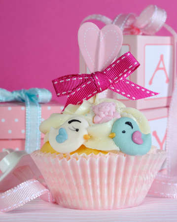 Baby girl cupcake with cute birds and ribbon closeup for baby shower or nursery concept  photo