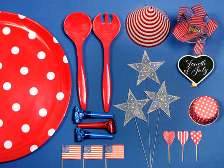 USA Happy Fourth of July, Independance Day, red white and blue party decorations with large red polka dot plate, red kitchen utensils, party hat, flags, stars and sample text on mini heart shape blackboard place setting marker.  photo