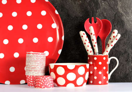 Modern Red and White Polka Dot Kitchen with large platter plate, cupcake pans, bowl, coffee mug, cutlery and serving spoons against black slate and white benchtop.  photo