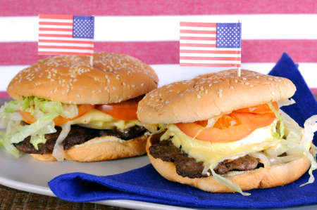 party with food: Happy Fourth of July, USA celebration party food, hamburgers wtih Stars and Stripes flags against red and white stripe background and natural recycled wood table. Stock Photo
