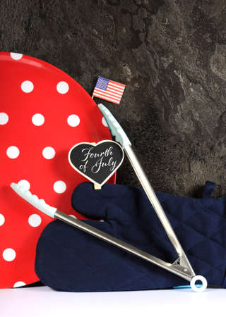 mini oven: Modern red, white and blue USA Fourth of July theme barbeque concept with large red polka dot plate, BBQ tongs, oven glove mitt, Stars and Stripes flag and sample text on heart shaped mini blackboard place setting, against black slate and white kitchen ba
