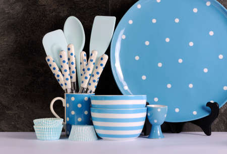 Modern Blue and White Polka Dot Kitchen with large platter plate, cutlery and kitchenware against black slate and white benchtop. photo