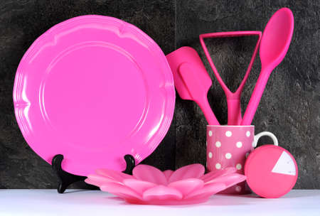 Modern Pink Polka Dot Kitchen with large platter plate, cutlery and kitchenware against black slate and white benchtop. photo