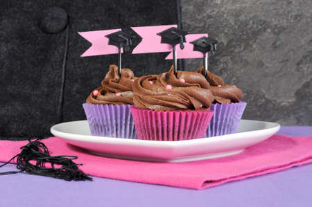 Graduation day pink and purple party cupcakes with chocolate frosting, on plate with large graduation cap in background, close up. photo
