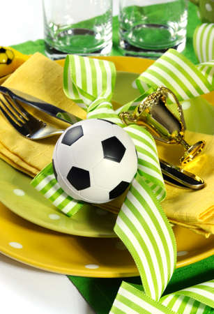 Soccer football celebration party table setting with pates, cutlery, glasses, trophy, soccer ball and decorations in yellow and green team colors  photo