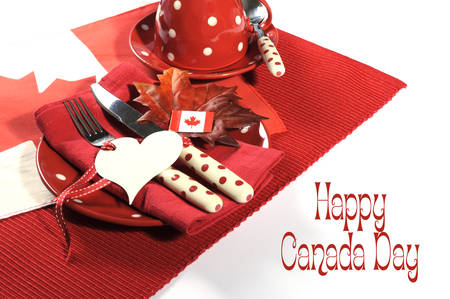 Happy Canada Day dinner party table setting in red and white polka dot china and cutlery on Canadian Maple Leaf flag with heart gift tag and sample text or copy space.