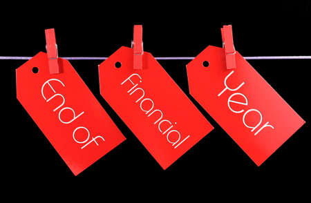 exemption: End of Financial Year red ticket sale tags hanging from pegs on a line against a black background.