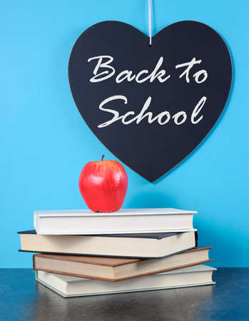 Back to School heart blackboard with red apple and stack of books on blue with black slate table background. photo