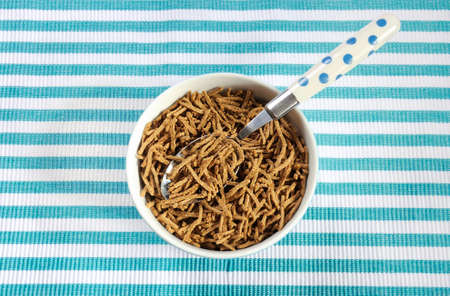 naturopath: Healthy diet high dietary fiber breakfast with bowl of bran cereal on aqua blue and white place mat.