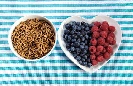 naturopath: Healthy diet high dietary fiber breakfast with bowl of bran cereal and berries on white heart plate on aqua blue and white place mat.