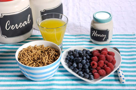 naturopath: Healthy diet high dietary fiber breakfast with bowl of bran cereal and berries on white heart plate on aqua blue with pineapple juice and jars.