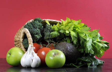 naturopath: Healthy diet health foods with shopping basket full of vegetables, green apples, garlic, tomatoes, broccoli, celery and avocado against a black slate kitchen top and red wall. Stock Photo