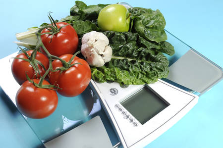 dietitian: Healthy diet and weight loss concept with healthy vegetables including tomatoes, garlic, green apples and spinach on modern weight scales against a pale blue background.
