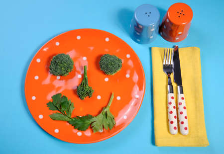 naturopath: Healthy diet health food concept with happy smiley face made from broccoli and celery on a fun orange polka dot plate with salt and pepper shakers, and colorful cutlery on a pale blue background.