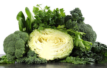 Healthy diet health foods with leafy green vegetables including cabbage, broccoli, broccolini, parsley, celery, silverbeet, and spinach on black slate kitchen top and white wall.