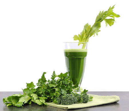 celery: Healthy diet health foods with nutritious freshly juiced green vegetable juice with celery, broccoli and parsley on black kitchen bench top against a white wall background. Stock Photo