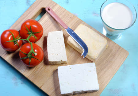 naturopath: Health food healthy diet food group, dairy free products, with soy milk, tofu, soy cheese, and goats cheese on wood chopping board and blue vintage tray background. Stock Photo