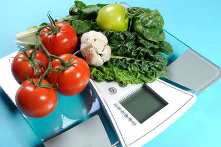 naturopath: Healthy diet and weight loss concept with healthy vegetables including tomatoes, garlic, green apples and spinach on modern weight scales against a pale blue background.