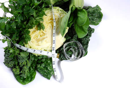 naturopath: Healthy diet health foods with leafy green vegetables including cabbage, broccoli, broccolini, parsley, celery, silverbeet, and spinach with measuring tape against a white background. Stock Photo