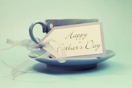 tea filter: Happy Fathers Day gift tag with a cup of coffee or tea for Dad in a blue polka dot cup and saucer against a blue background, with retro vintage style filter. Stock Photo