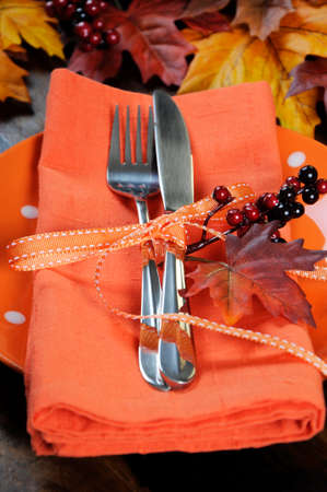 Autumn Fall background with red, brown and yellow leaves, orange pumpkin and monarch butterfly on dark recycled rustic wood table  with orange table place setting - vertical closeup. photo