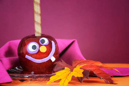 Sugar apple: Happy smiling crazy face red toffee apple candy for trick or treat Halloween food against a bright dark pink red and orange background, closeup.