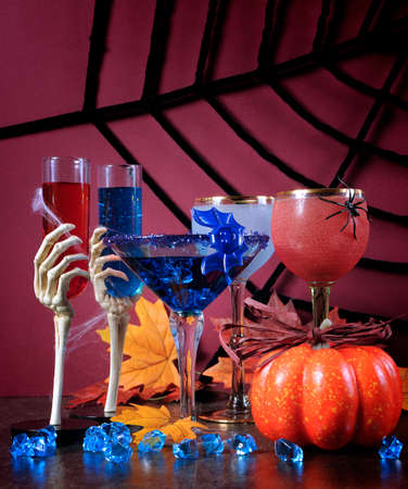 ghoulish: Happy Halloween ghoulish party cocktail drinks with spider web and decorations on purple background. Stock Photo