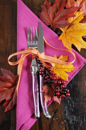 october 31: Bright and colorful pink, orange and black modern Thanksgiving or Halloween autumn fall place setting on dark recycled wood table.