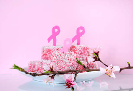 lamington: Pink Ribbon Day charity Australian style pink heart shape small lamington cakes with spring blossom and Pink Ribbon symbols  against a pink background. Stock Photo