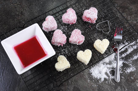 lamington: Making Australian style pink heart shape small lamington cakes on baking rack with strawberry sauce and coconut.