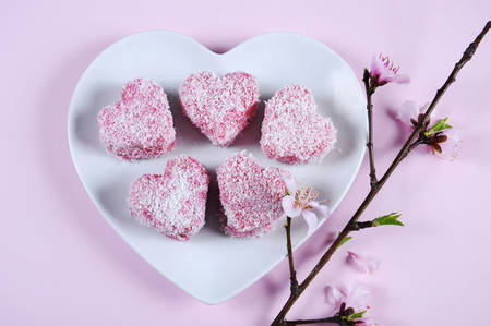 lamington: Homemade Australian style pink heart shape small lamington cake on heart shape white plate with spring blossom on a pink background.