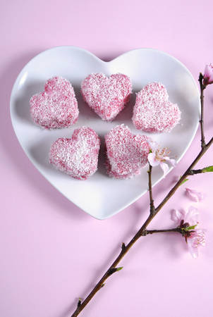 tucker: Homemade Australian style pink heart shape small lamington cake on heart shape white plate with spring blossom on a pink background. Vertical.