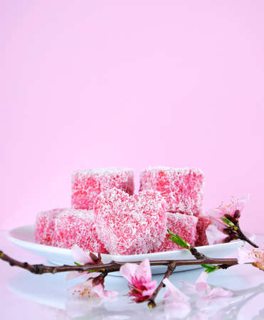 Homemade Australian style pink heart shape small lamington cakes with spring blossom on a reflective table against a pink background. Vertical with copy space.