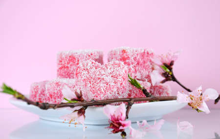 tucker: Homemade Australian style pink heart shape small lamington cakes with spring blossom on a reflective table against a pink background. Stock Photo