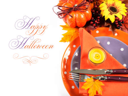 Happy Halloween or Thanksgiving party table place setting with Autumn Fall leaves, pumpkin, lit candle, and orange and purple tableware on white background, with sample text.