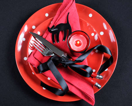 Elegant red and black theme Halloween party dining Table place setting with plates, cutlery, black cat and lit candle. photo