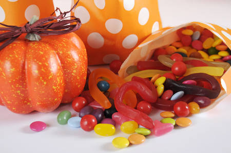 Row of Happy Halloween orange polka dot trick or treat paper bags with multi-color candy against and orange and white background. Close up.