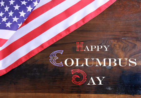 Happy Columbus Day greeting message text on dark rustic recycled wood background with USA stars and stripes flag.