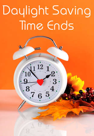 savings: Daylight savings time ends in autumn fall with clock concept and text message on orange background.