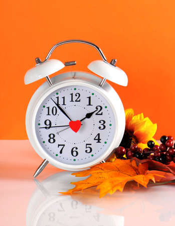 Daylight savings time ends in autumn fall with clock concept on orange background. photo