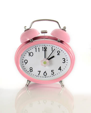 daylight savings time: Daylight savings time pink clock on reflective glass concept against a white background. Stock Photo