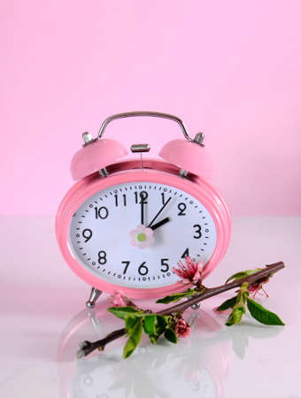 daylight savings time: Daylight savings time begins clock concept for start at Spring against a pink background. Stock Photo